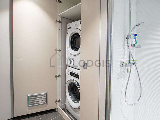 Bathroom equipped with washing machine, dryer, wardrobe, shelves