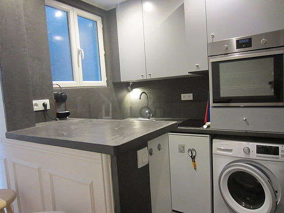 Kitchen equipped with washing machine, refrigerator, stool