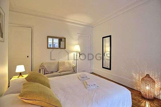 Chambre très lumineuse équipée de canapé, table de chevet