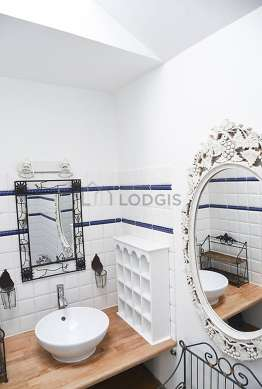 Pleasant and very bright bathroom with windows and with wooden floor