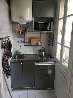 Kitchen equipped with hob, refrigerator, stool
