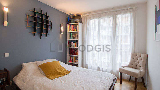 Bright bedroom equipped with 1 armchair(s), bedside table
