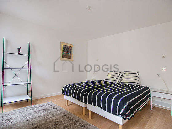 Very bright bedroom equipped with air conditioning, bedside table