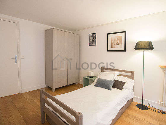 Very bright bedroom equipped with desk, closet, bedside table