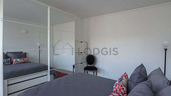 Very bright bedroom equipped with 1 armchair(s), bedside table