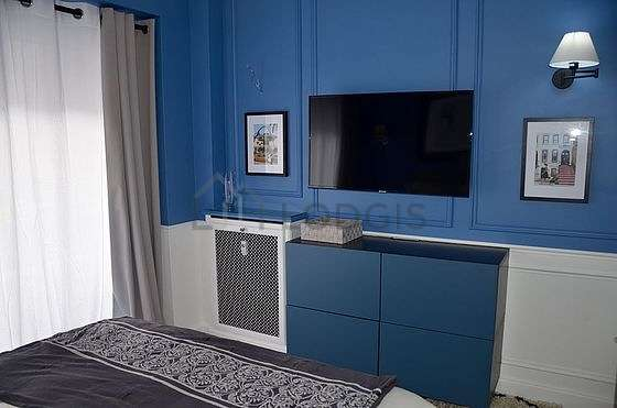 Bright bedroom equipped with tv, bedside table