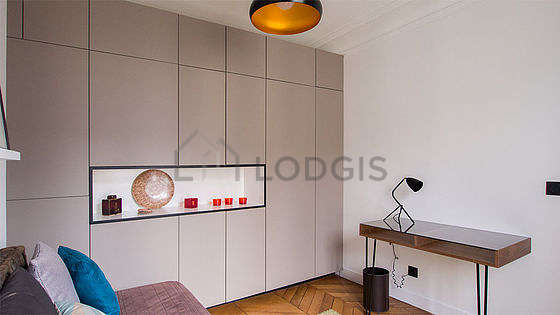 Bright bedroom equipped with desk, wardrobe, cupboard