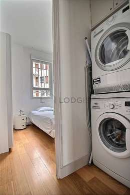 Laundry room with wooden floor and equipped with washing machine, dryer