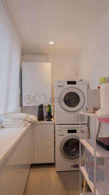 Beautiful laundry room with tile floor and equipped with washing machine, dryer