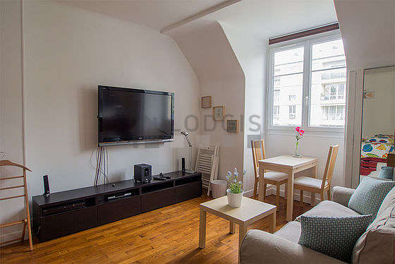 Quiet living room furnished with 1 bed(s), tv, cupboard, 2 chair(s)