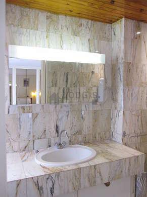 Agréable salle de bain claire avec fenêtres et du marbre au sol