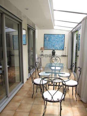 Superbe véranda de 12m² avec du carrelage au sol et une vue sur jardin