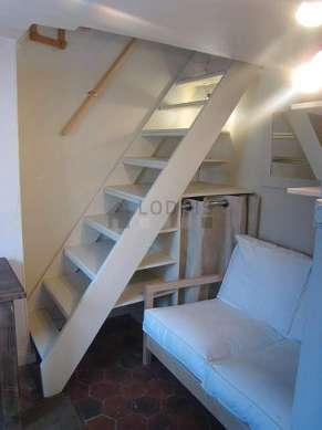 Mezzanine sous belle hauteur de plafond avec de la moquette au sol
