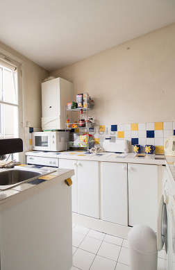 Kitchen equipped with dryer, refrigerator, crockery, stool