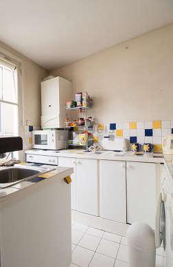 Cuisine équipée de sèche linge, réfrigerateur, vaisselle, tabouret