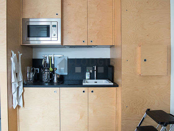 Kitchen equipped with hob, refrigerator, cookware