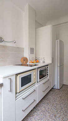 Kitchen equipped with hob, refrigerator, crockery, stool