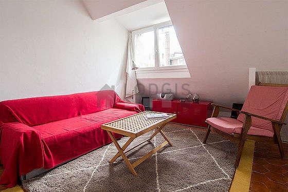 Grand salon de 20m² avec des tomettes au sol