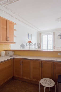 Bright kitchen with windows and balcony facing the road