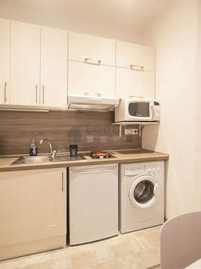 Cuisine équipée de lave linge, réfrigerateur, vaisselle, tabouret