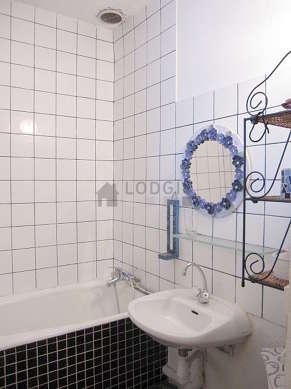 Agréable salle de bain claire avec fenêtres et des tomettes au sol