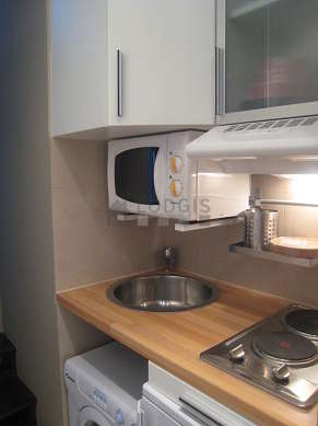 Kitchen equipped with hob, refrigerator, freezer, cookware