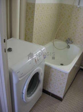 Bathroom equipped with washing machine, bath tub, shower in bath tub