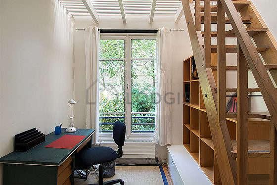 Beau bureau avec du parquet au sol, équipé de bureau, bibliothèque, etagère