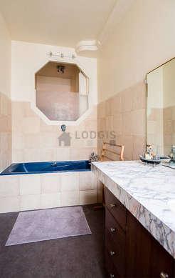 Belle salle de bain claire avec fenêtres et du linoleum au sol