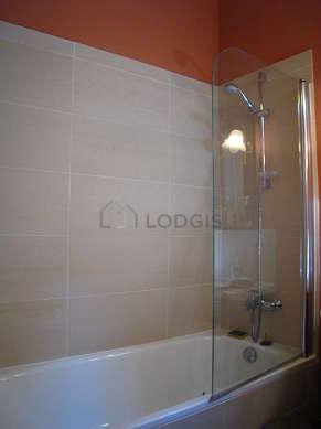 Salle de bain avec fenêtres et des tomettes au sol