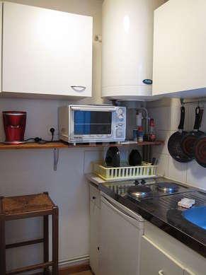 Cuisine équipée de plaques de cuisson, réfrigerateur, vaisselle, tabouret