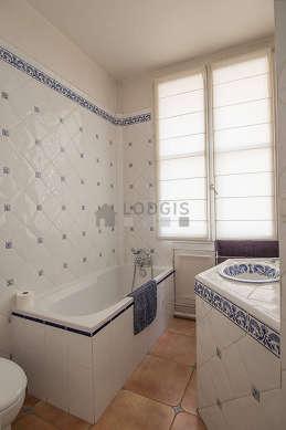 Belle salle de bain claire avec fenêtres et du parquet au sol