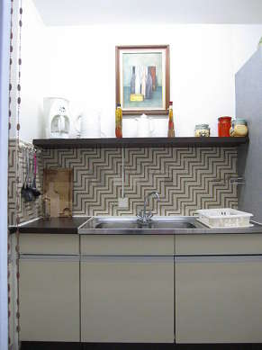 Kitchen equipped with hob, refrigerator, hood, cookware